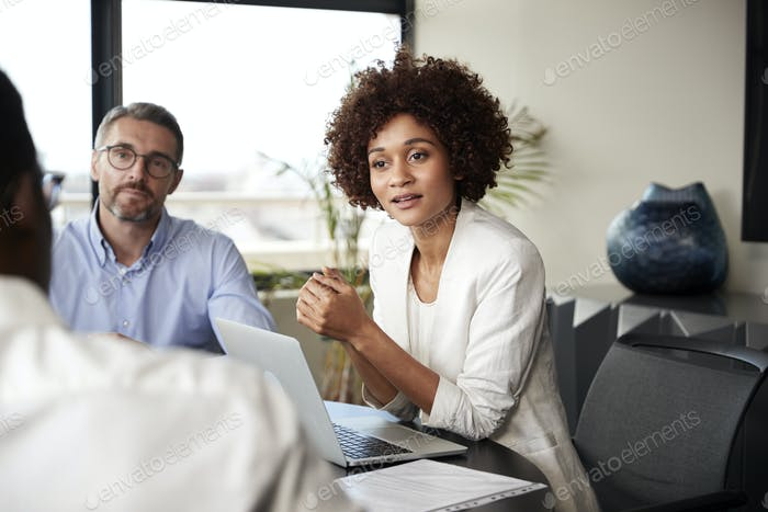 Millennial black businesswoman listening to colleagues at a corporate business meeting, close up