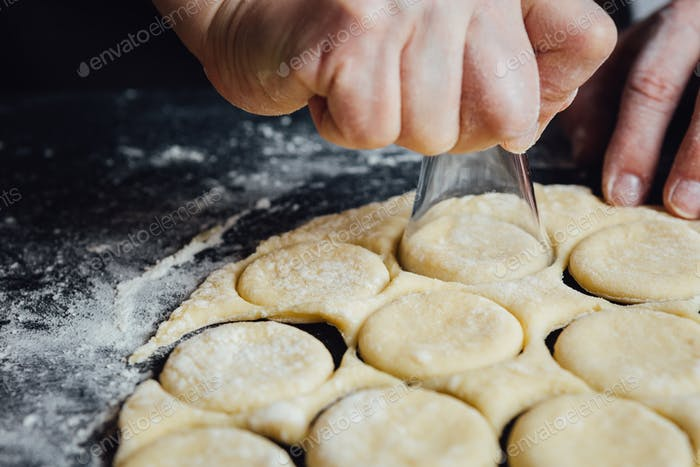 Person shaping cookies with shot glass
