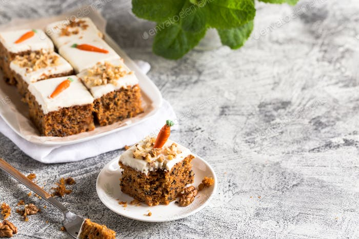 pieces of carrot cake with walnuts with icing cream
