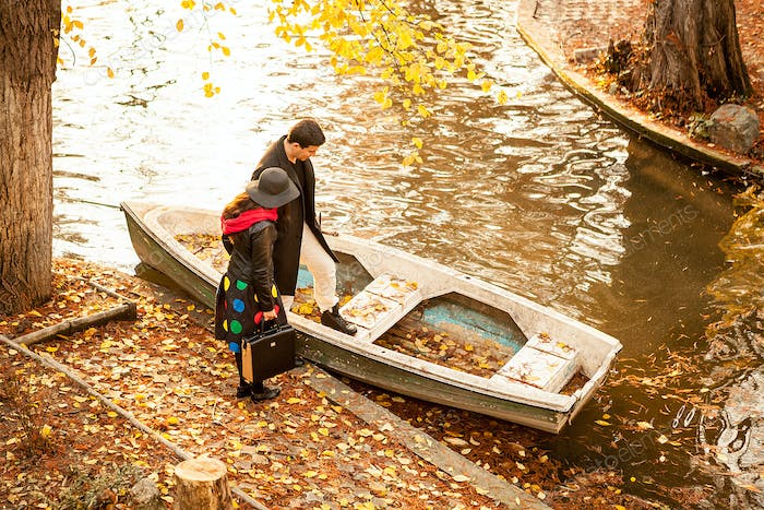 Couple next to a boat in park