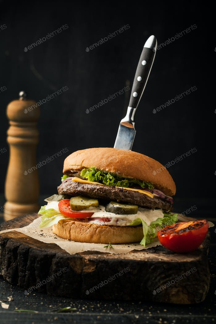 Delicious beef burger with knife and spices