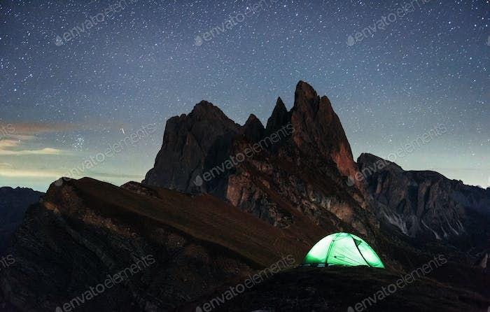 Dawned sun. Night photo of Seceda dolomites mountains. Tourists resting in the green tent