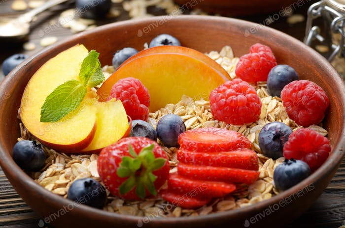 Fruit healthy muesli with peaches strawberry almonds and blackbe