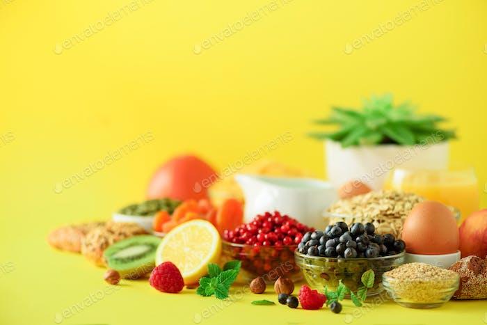 Healthy breakfast ingredients, food frame. Oat and corn flakes, eggs, nuts, fruits, berries, toast