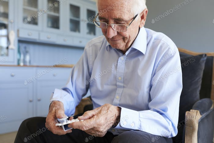 Senior Man Using Pill Popper To Remove Medication From Packet