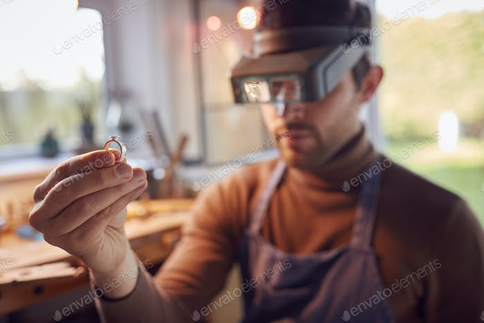 Close Up Of Male Jeweller Looking At Ring Through Headband Magnifiers In Studio