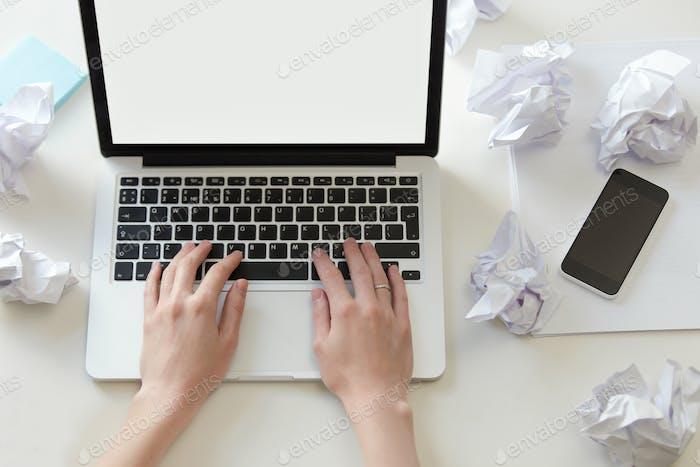 Hände arbeiten mit einem Laptop auf dem weißen Bürotisch