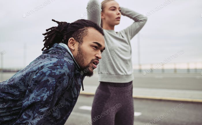 Focused young couple preparing for a run togeher