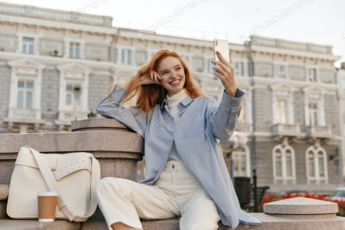 Charming young lady making selfie in city against buildings background. Attractive foxy girl with b