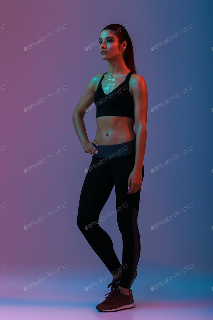 Full length portrait of beautiful slim girl in sportswear posing