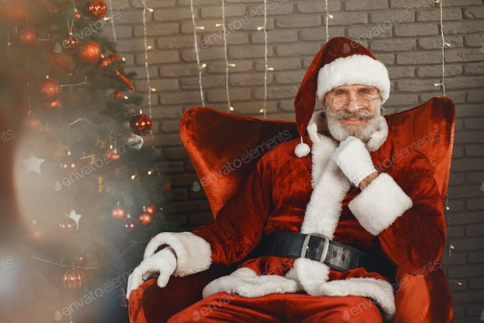 Man in santa claus costume sitting on a chair