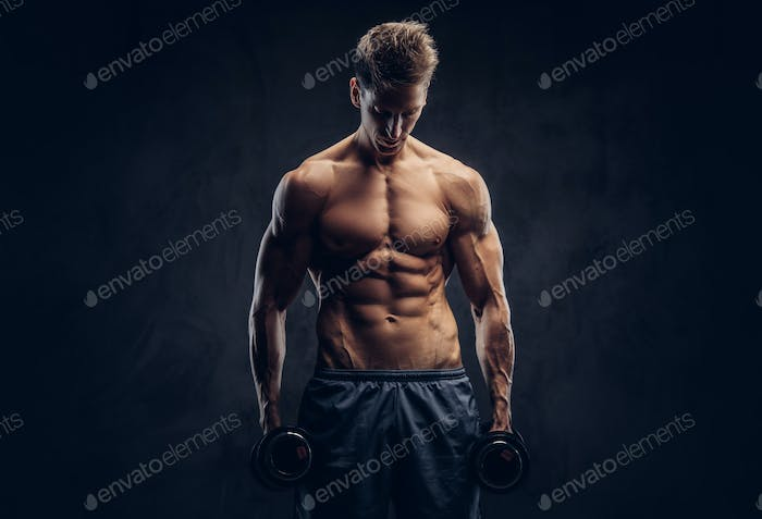 Handsome shirtless man with muscular ectomorph body doing the exercises with dumbbells.