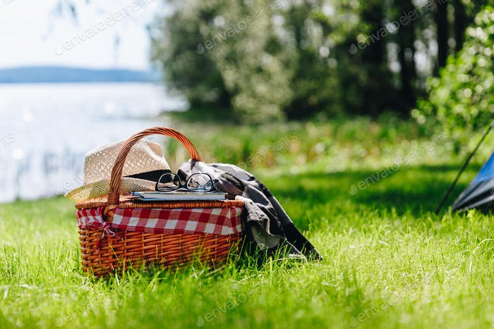 Picnic basket with hat, book and grasses on the grass at the summer sunny day.