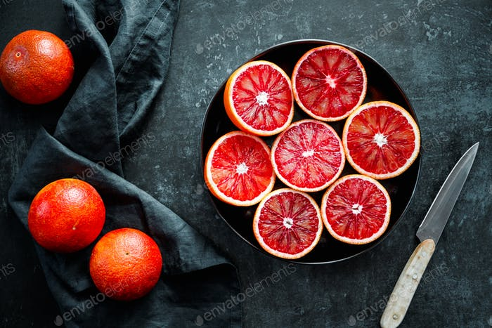 Cutted blood oranges in a plate on a black background.