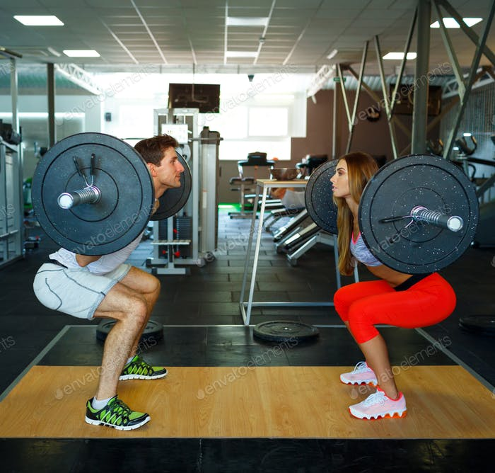 Athletic man and woman with barbell doing squats in the gym