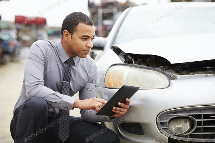 Loss Adjuster Using Digital Tablet In Car Wreck Inspection