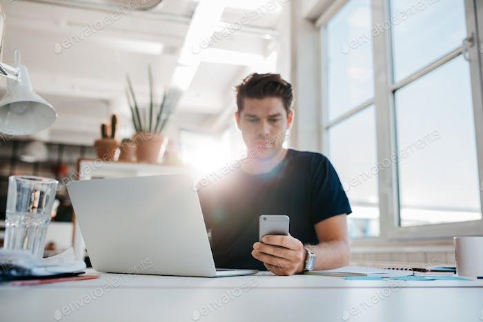 Geschäftsmann liest SMS auf seinem Handy.