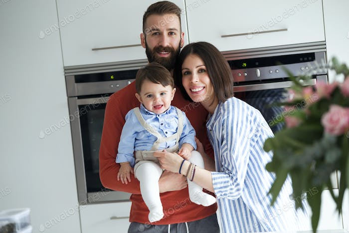 Pretty young parents with baby looking at camera in the kitchen at home.