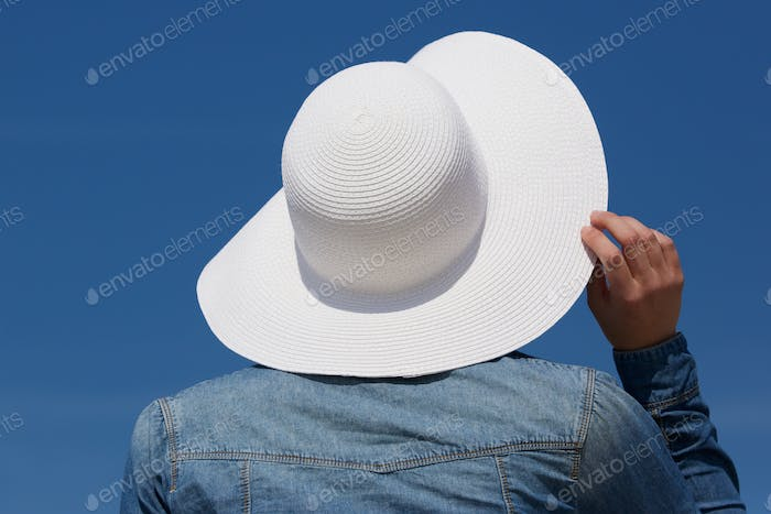 Back of a young woman with sun hat