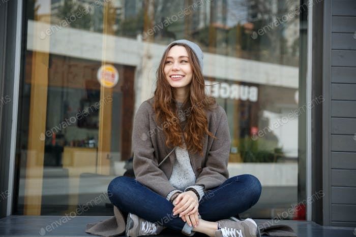 Cheerful attractive young woman sitting outdoors in the city