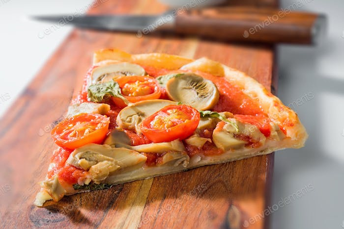 serving of mushroom and tomato pizza served on wooden board