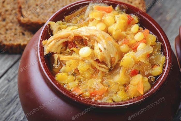 Maische Suppe im Topf, Teller mit dunklem Brot. Hintergrund aus Holz.