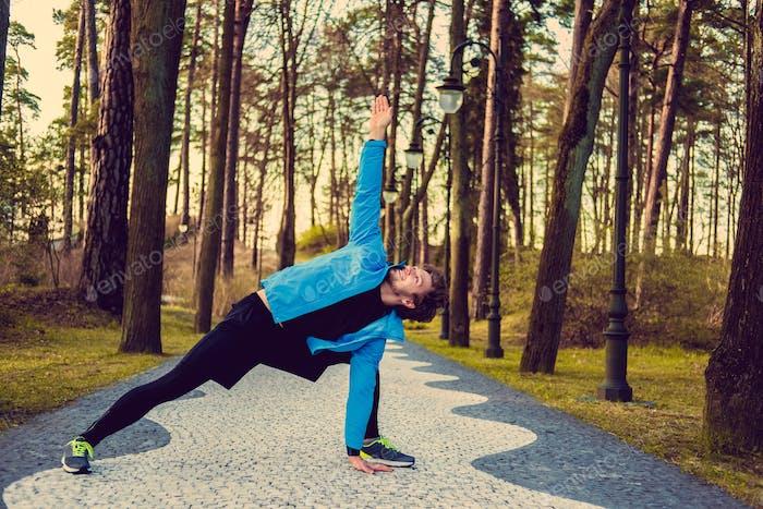 Flexible fitness man in a blue sports jacket.
