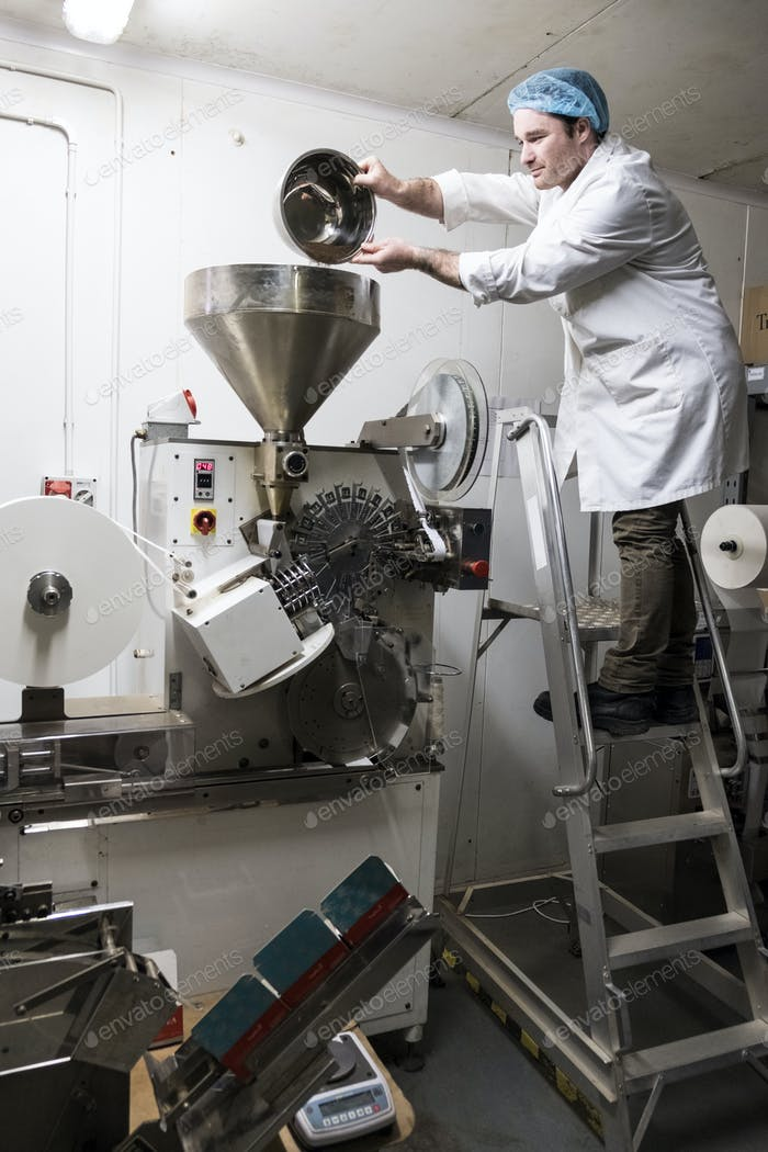 Man wearing white coat standing on a ladder, pouring tea leaves into large funnel of a machine.