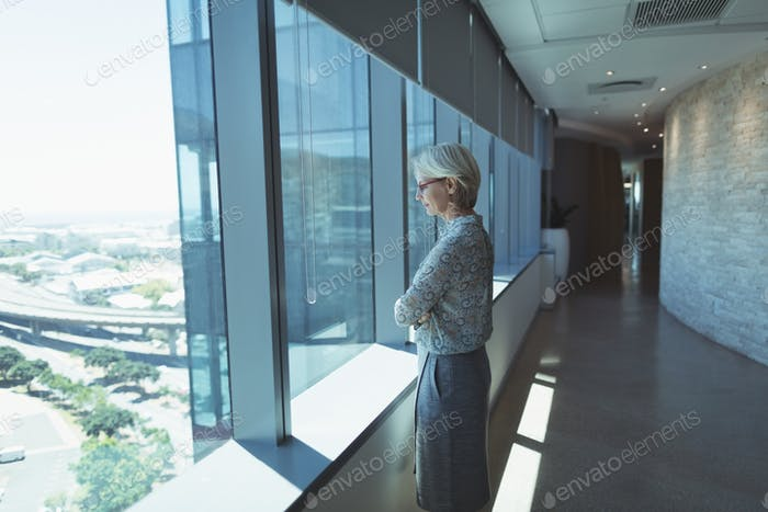 Thoughtful businesswoman standing by window