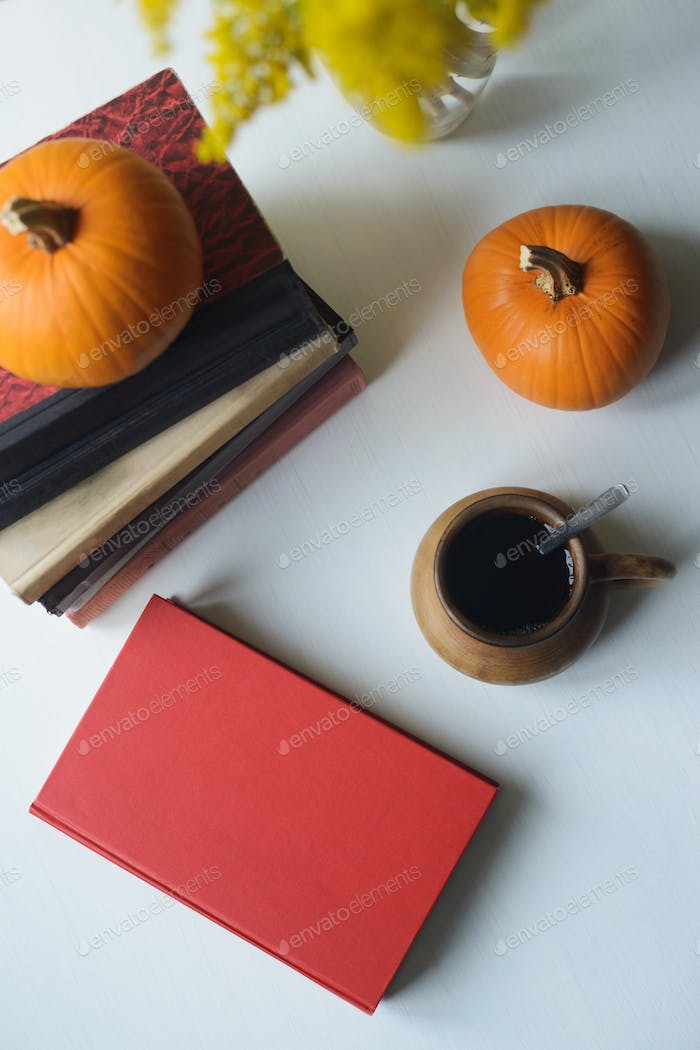 autumn flat lay still life with books, pumpkins, cup