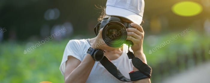 Woman photographer taking photo outdoors