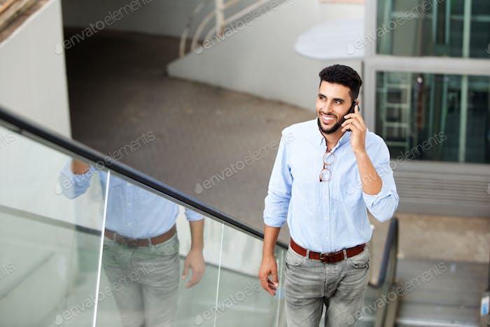 sonriente joven árabe hombre de pie en escalera mecánica hablando en móvil