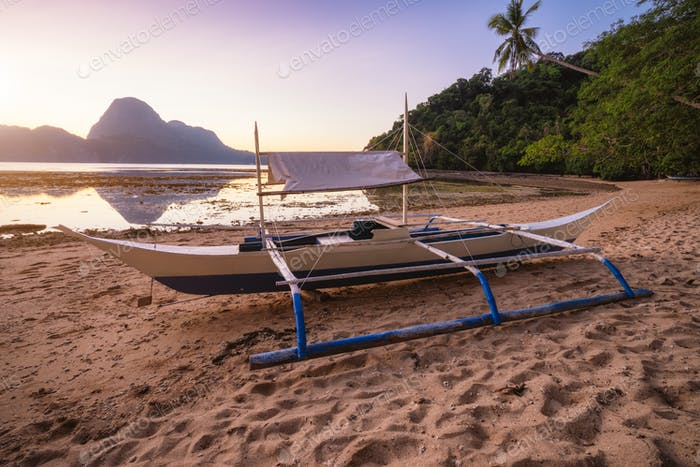 View of El Nido bay with local banca boat in front at low tide, picturesque scenery in the afternoon