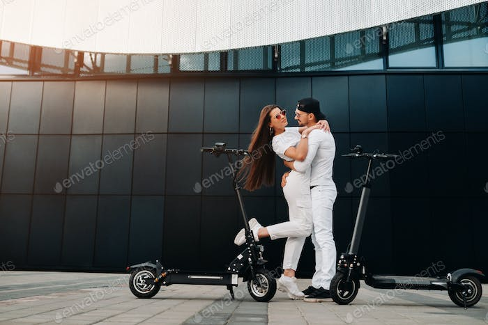 A couple on electric scooters embrace in the city, a couple in love on scooters