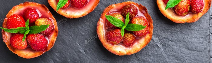 Banner of Homemade strawberries tarts on slate plate, black background.