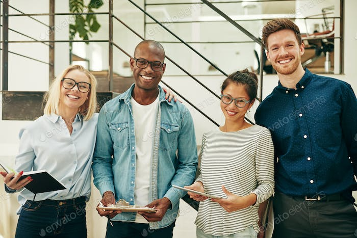 Diverse businesspeople laughing while working together in an office