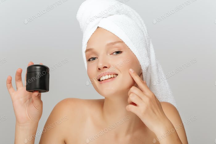 Portrait of young smiling woman without makeup with white towel