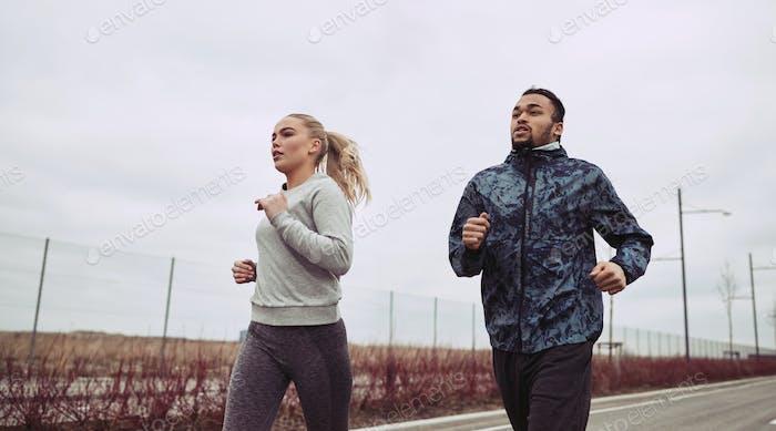 Разнообразная молодая пара в спортивной одежде бежит вдоль загородной дороги