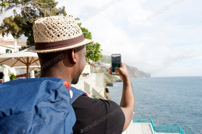 behind of african american travel man with bag looking taking selfie by the sea