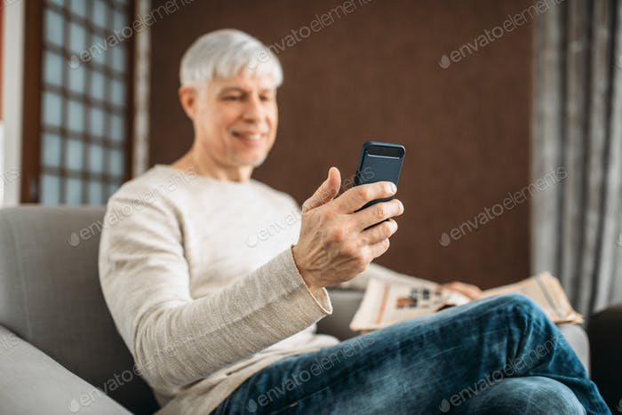 Adult man with phone sitting on couch at home