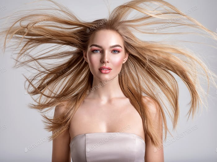 Portrait of a blonde beautiful woman with a long straight light hair. Flying hair.