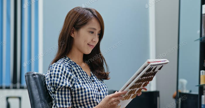Woman choose the color on book at the hair salon