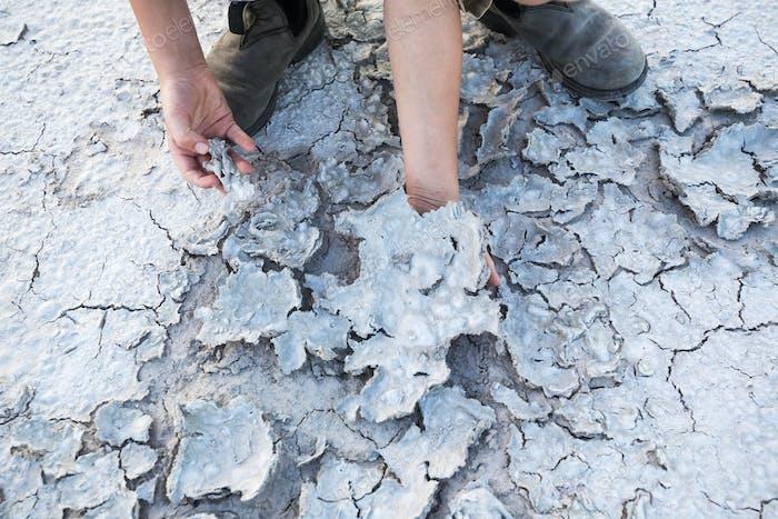 A child, boy exploring the cracked salt crust and evaporation at a salt pan.
