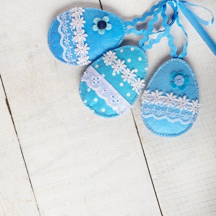 Handgefertigtes Patchwork blau Filz Ostereier auf weißem Holztisch