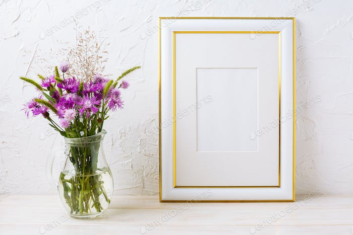 Gold decorated frame mockup with purple burdocks in glass