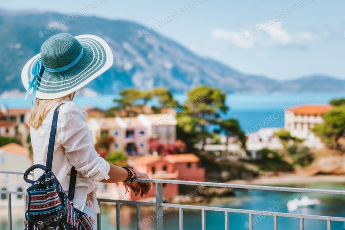 Tourist woman wearing blue sun hat enjoying top view of colorful tranquil village Assos on sunny day