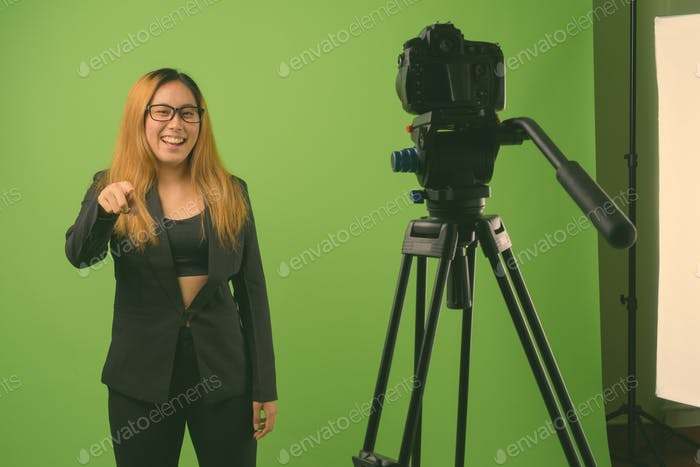 Young Asian businesswoman against green background