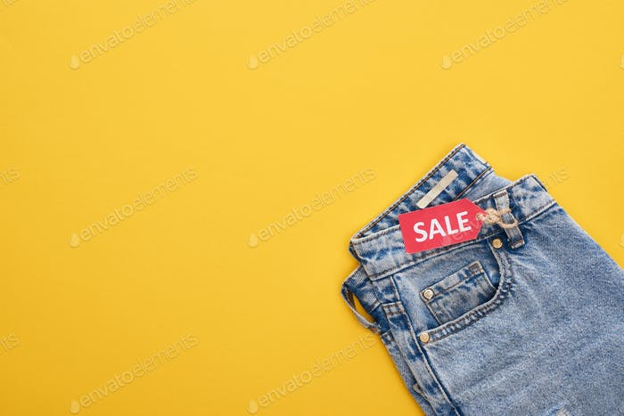 Top View of Jeans With Sale Label on Yellow Background