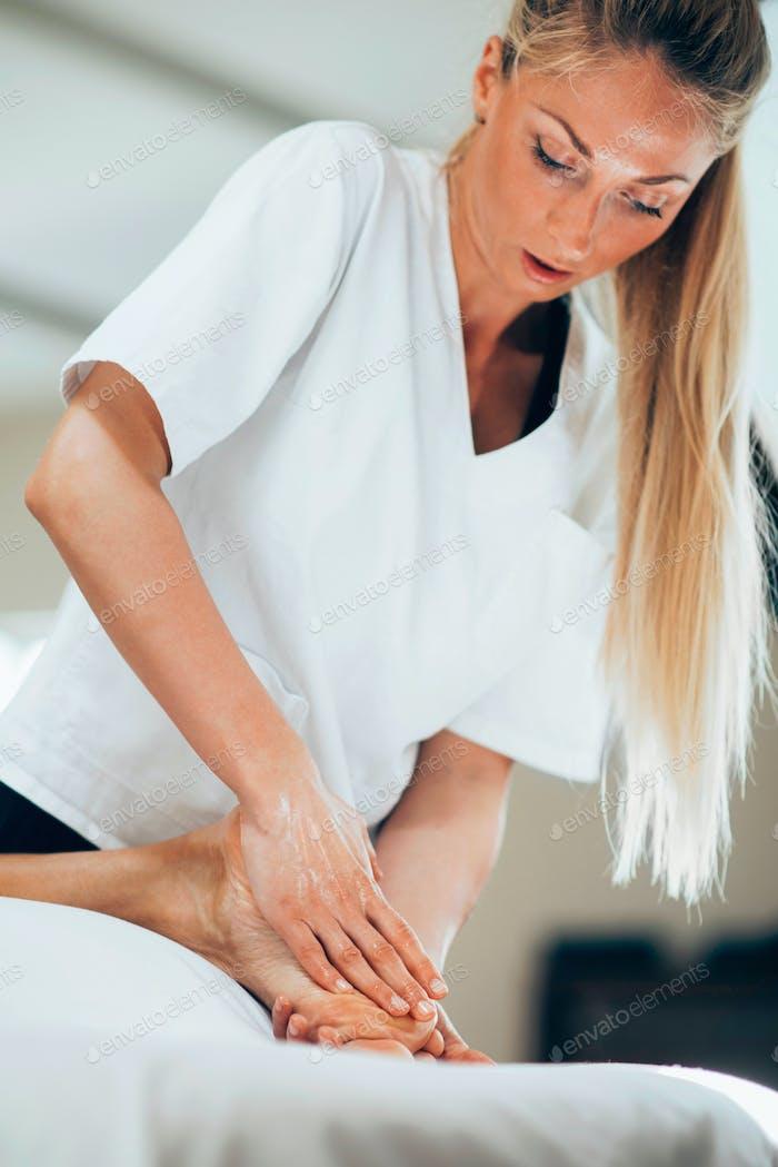 Pretty masseuse doing foot massage