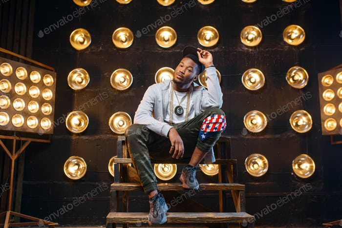 Black rapper in cap poses, perfomance on stage